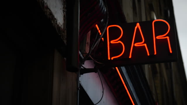 selective focus shot of a red neon bar sign at dusk - bar video stock e b–roll