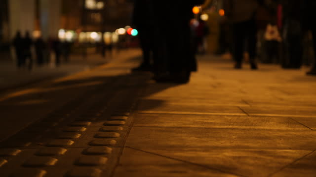 Selective focus shot of people waiting on a tram platform in Manchester at night