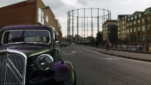 vidéos et rushes de selective focus street scene with vintage car and gas holder - hackney