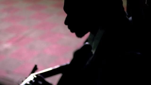 selective focus tilt down silhouettes of black woman behind black man playing guitar / nova scotia - 横顔点の映像素材/bロール