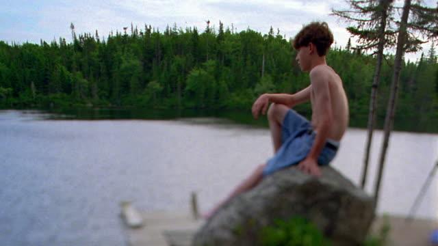 vidéos et rushes de selective focus wide shot boy in swimsuit sitting on rock at edge of mountain lake / nova scotia - profil