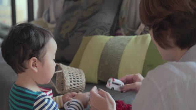 4 k 、セレクティブフォーカスます。若い母と子のリビングルームがございます。東京,日本 - 親点の映像素材/bロール