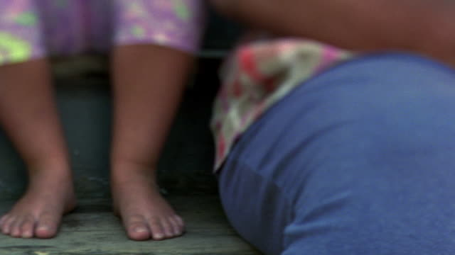 stockvideo's en b-roll-footage met selective rack focus close up pan from bare feet of two children to lap of woman sitting on steps / nova scotia - alleenstaande moeder