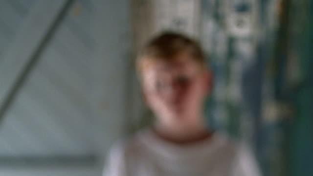 Selective rack focus medium shot redheaded boy looking serious against wooden wall / Nova Scotia, Canada