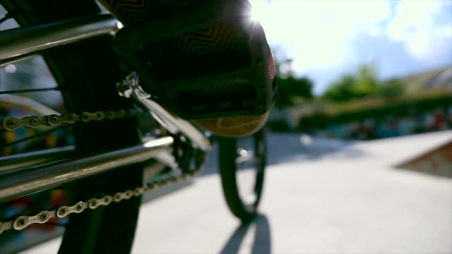 A selective-focus view of a young man riding a BMX bicycle in a concrete skate park. - Slow Motion