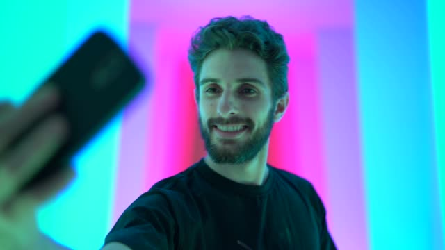 self portrait of a beautiful man at colored tunnel - selfie video stock e b–roll