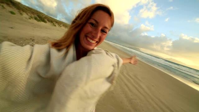 Självporträtt av en glad ung kvinna på stranden