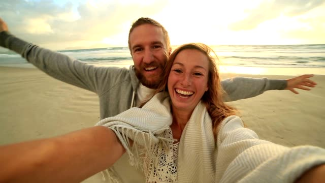 self portrait of happy young couple on beach at sunset - baia delle isole nuova zelanda video stock e b–roll