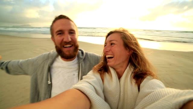 Selbstporträt von glückliches junges Paar am Strand bei Sonnenuntergang
