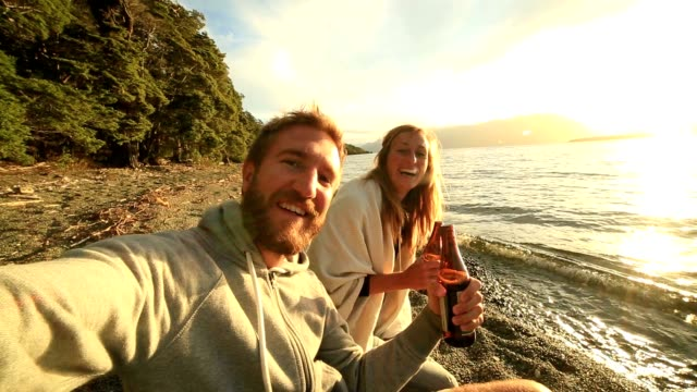 self portrait of young couple enjoying drink by the lake - new zealand stock videos & royalty-free footage
