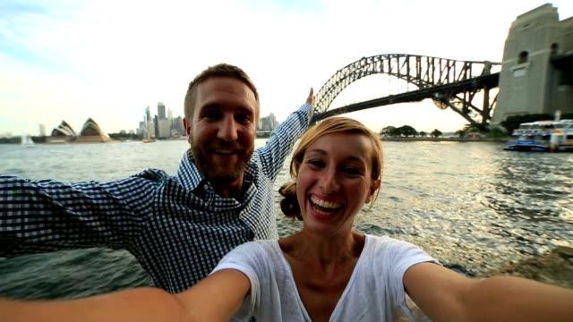 vídeos de stock e filmes b-roll de self portrait of young couple with sydney skyline - ponte