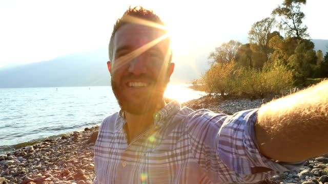 Self portrait of young man by the lakeshore in summer