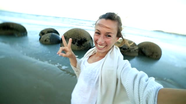 Self portrait of young woman at the Moeraki boulders-New Zealand