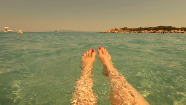 Selfie Beach Feet. Woman relaxing floating in the water.