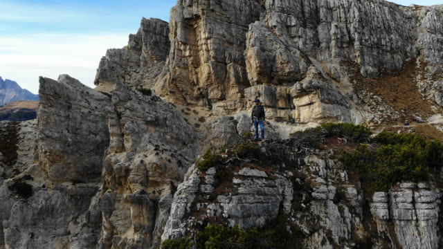 vidéos et rushes de selfie drone of a hiker facing the sharp dolomite mountains in the italian alps from top of a hill. - vertige