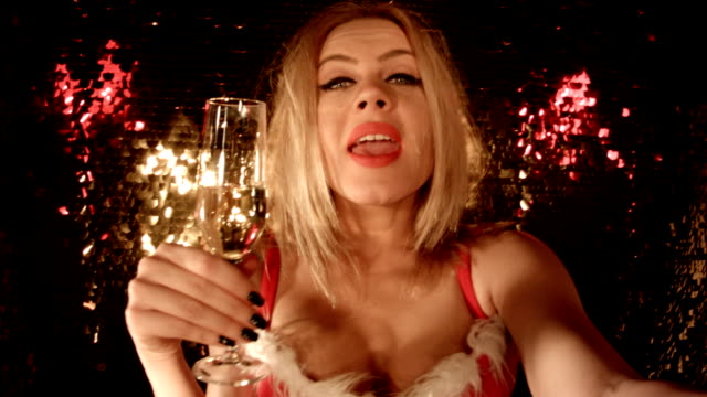 Selfie From a Nightclub. 'Merry Christmas' 'Happy New Year' Sensual Blonde Girl Taking a Selfie in Front of Glittering Background at Nightclub.