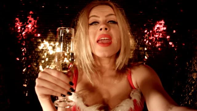 """vídeos y material grabado en eventos de stock de selfie en un club nocturno. año'merry christmas'""""sensual blonde girl tomando un autorretrato en frente de fondo brillantes en un club nocturno. - día de fin de año"""
