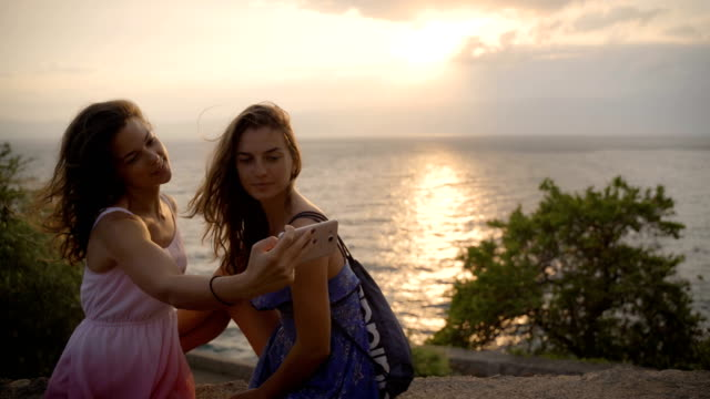 selfie fun girls taking picture at cool sunset.summer holidays, girls at smartphone camera taking self-portrait on their travel vacations.best friends girls make picture at sunset - cinemanis videography stock videos & royalty-free footage