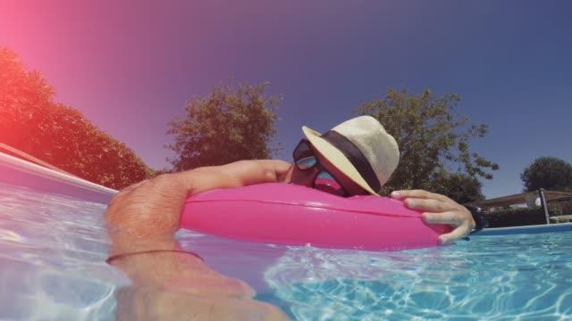 Selfie: Mann im Schwimmbad mit Luftmatratze schweben