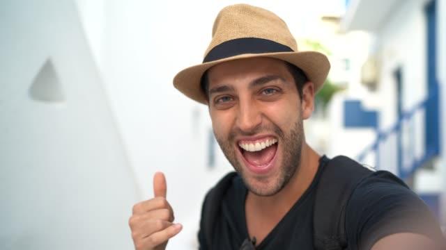 vídeos de stock, filmes e b-roll de selfie de um homem novo feliz em mykonos, greece - grécia