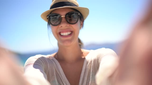 vídeos de stock e filmes b-roll de selfie of a young woman wearing sunglasses in front of a swimming pool - greece