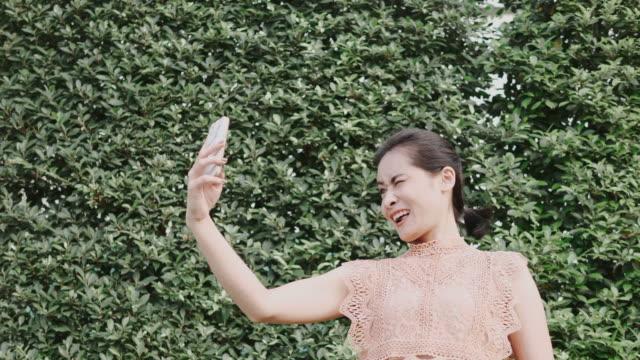 selfie schöne asiatin nimmt ein bild im garten - zuschnappen stock-videos und b-roll-filmmaterial