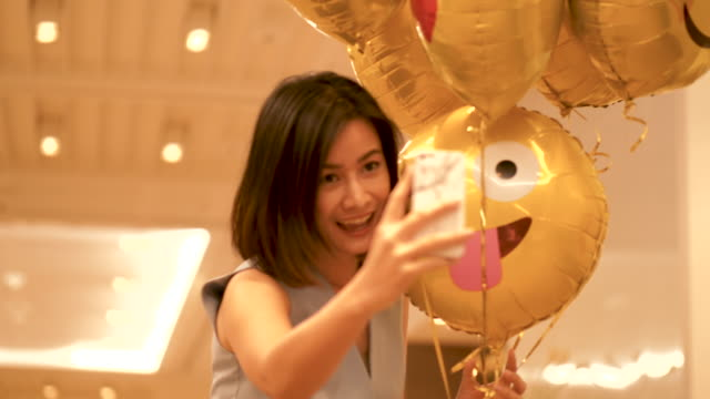 Selfie of beautiful Thai business woman is using smartphone for taking a picture with cute yellow balloon with her positive emotion and happiness