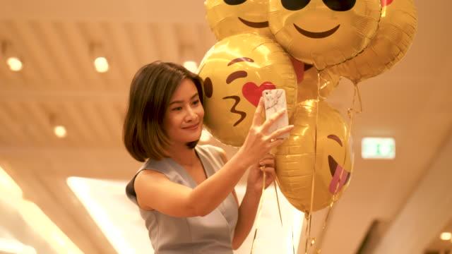 selfie schöne thai business-frau ist smartphone verwenden, um ein foto mit niedlichen gelben ballon mit ihrer positiven emotionen und freude - zuschnappen stock-videos und b-roll-filmmaterial