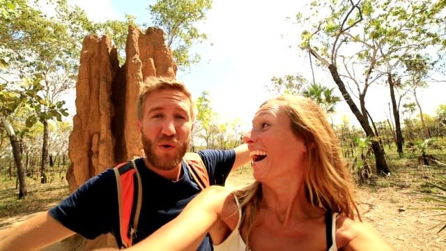 selfie of caucasian couple with enormous termite mound, australia - travel destinations stock videos & royalty-free footage
