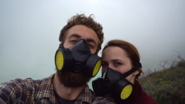 selfie of couple in masks on ijen sulfur minings - java stock videos & royalty-free footage