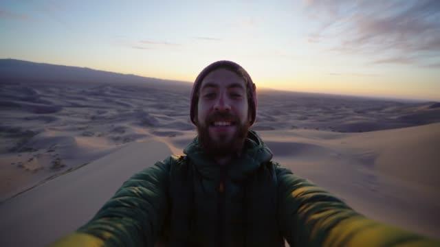 selfie von mann sitzt auf düne in gobi wüste bei sonnenuntergang - einsamkeit stock-videos und b-roll-filmmaterial