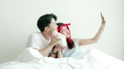 Selfie of Thai couple while showing gift box with Valentine and birthday celebration