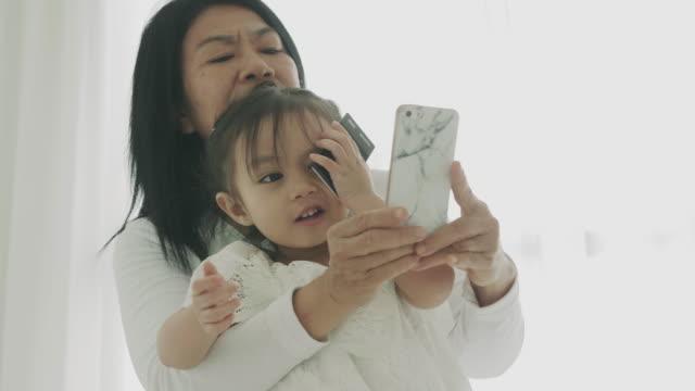 タイ人の母親と娘のタイの家族のスマート電話、近代的なライフ スタイルを使用しての selfie - カメラ点の映像素材/bロール