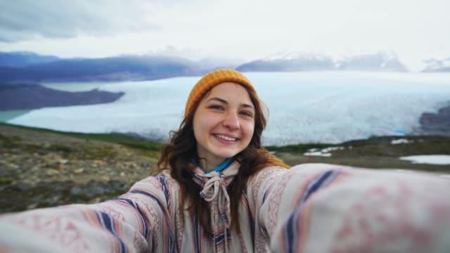 stockvideo's en b-roll-footage met selfie van vrouw op de achtergrond van grijze gletsjer in torres del paine nationaal park - argentina