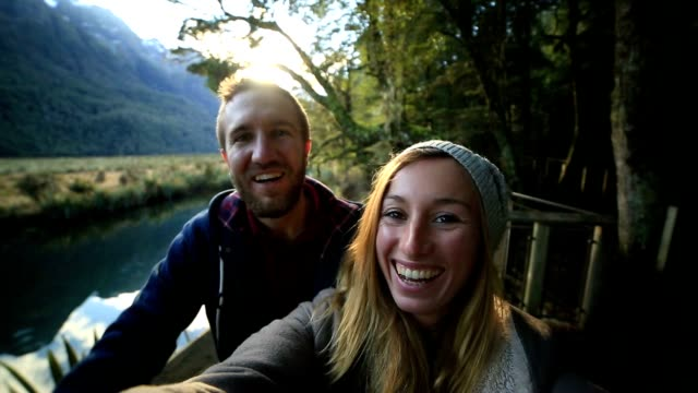 Selfie of young couple in lake mountain landscape