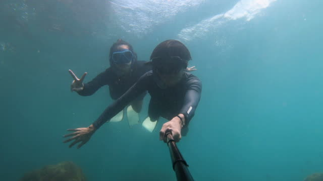 selfie of young couple snorkeling in the sea - free diving stock videos & royalty-free footage