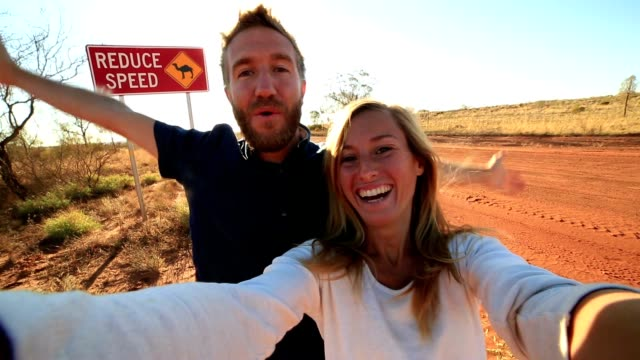 selfie of young couple standing by camel warning sign - road warning sign stock videos & royalty-free footage
