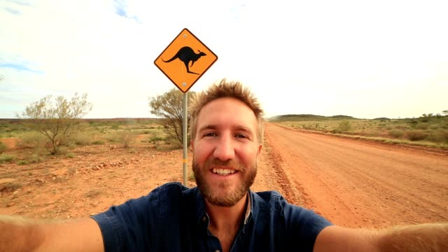 selfie of young man in australia standing near kangaroo crossing sign - road warning sign stock videos & royalty-free footage