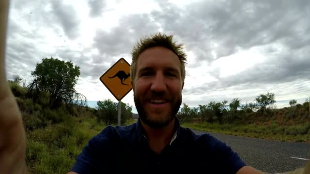 selfie of young man in australia standing near kangaroo sign - road warning sign stock videos & royalty-free footage
