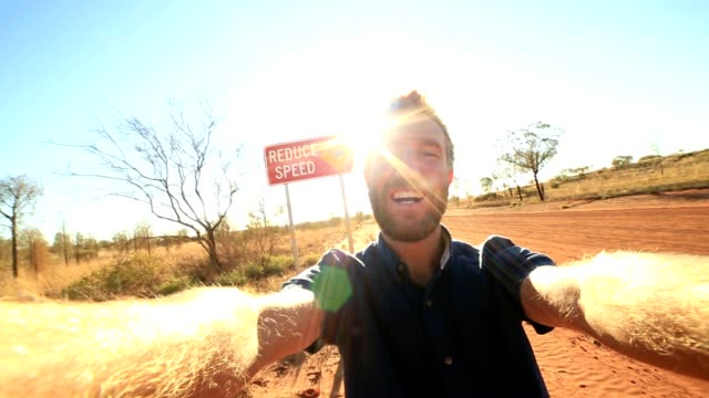 Selfie of young man standing by Camel warning sign