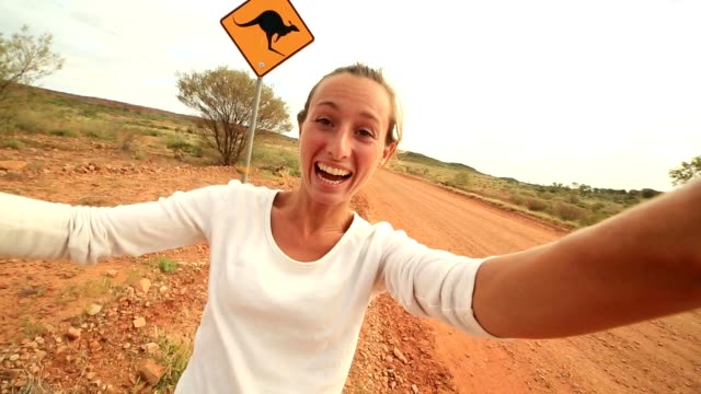 selfie of young woman in australia standing near kangaroo sign - road warning sign stock videos & royalty-free footage