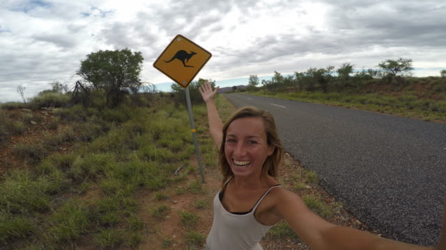 selfie of young woman in australia standing near kangaroo sign-4k - road warning sign stock videos & royalty-free footage