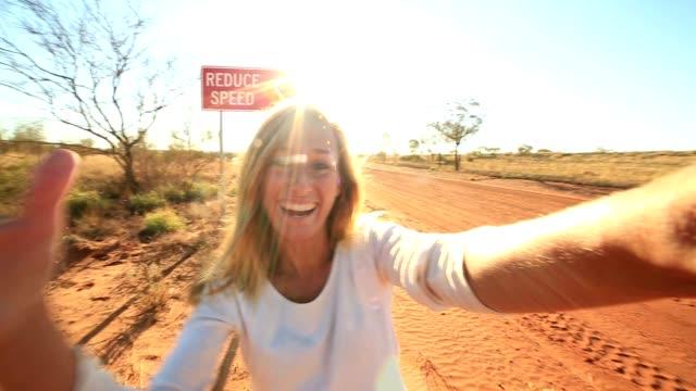 Selfie van jonge vrouw permanent door Camel waarschuwingsbord