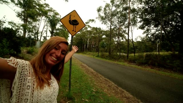 selfie of young woman standing near emu warning sign, australia - road warning sign stock videos & royalty-free footage