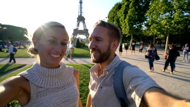 selfie porträt eines jungen paares in paris stehen in der nähe des eiffelturms - eiffelturm stock-videos und b-roll-filmmaterial