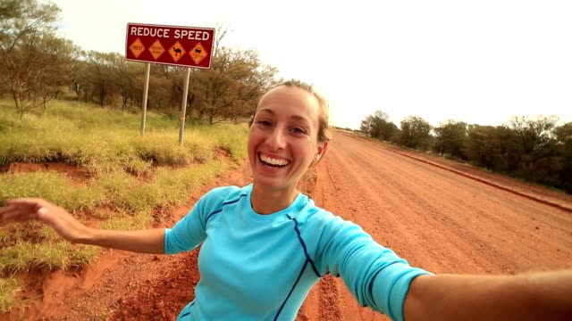 selfie portrait of a young woman in the australian outback - road warning sign stock videos & royalty-free footage