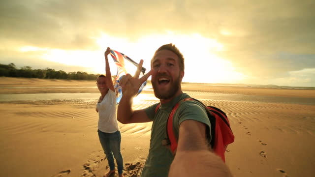 Selfie portrait of two young adults on beach holding flag