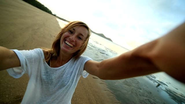 Selfie portrait of young woman on the beach