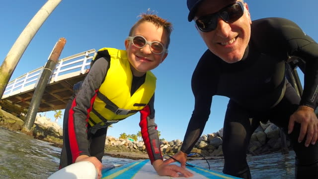 selfie pov of a boy and his father paddling an sup stand-up paddleboard in a marina. - slow motion - using a paddle stock videos & royalty-free footage
