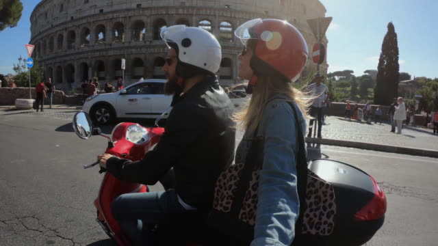 selfie scooter riding: tourist couple on the motorbike by the coliseum - motor scooter stock videos & royalty-free footage